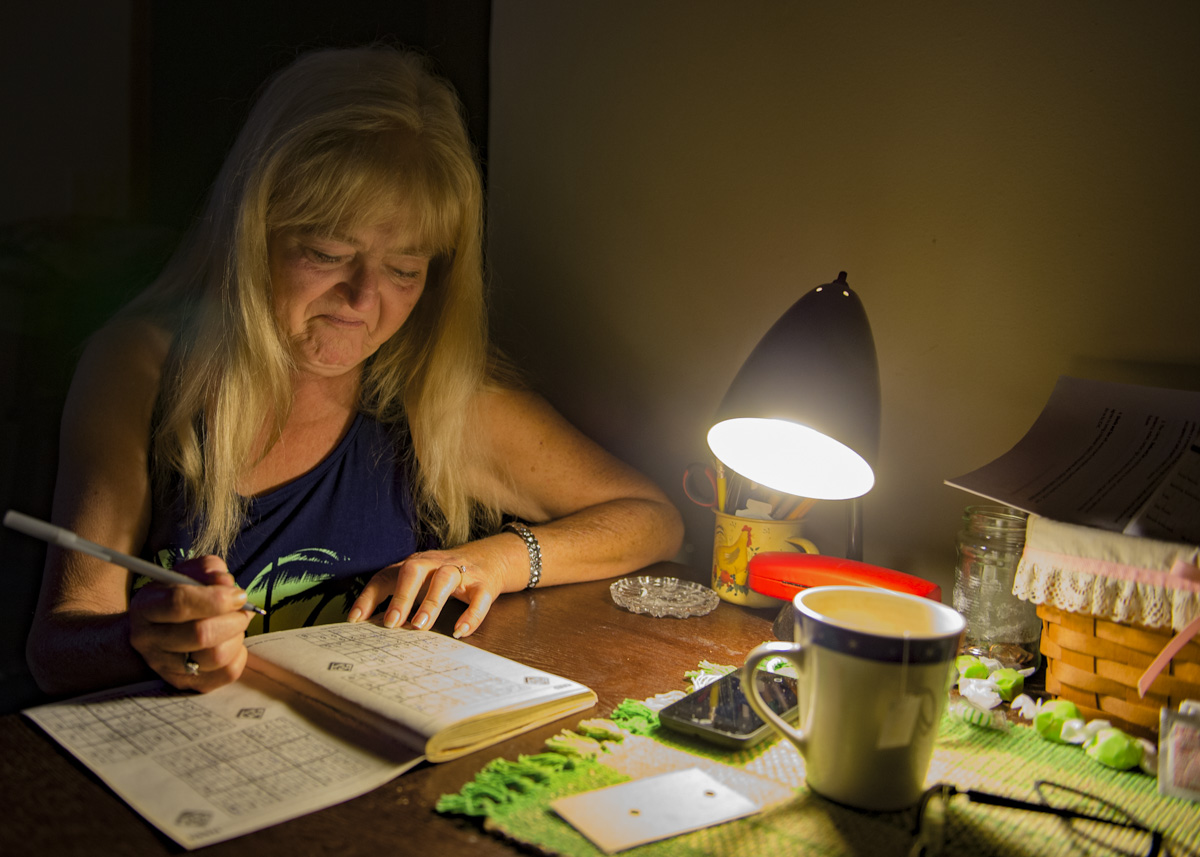 Sheliah Price works on a Sudoku puzzle in her transitional home, which she moved into after her mobile home burned down in June.