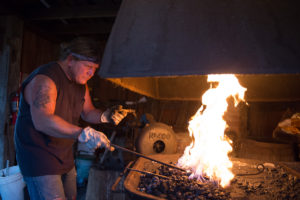 Rob Miller heats a piece of metal in the primary forge of the blacksmith shop in McConnelsville.