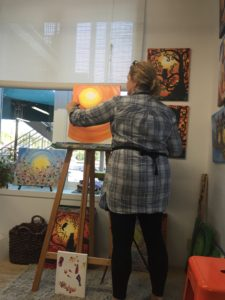 Owner, Bobbi McKinnon, leads a group painting session in painting a Fall themed canvas.