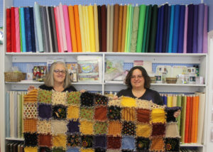 Jeana Paglialunga and her mother, Joyce, hold up a quilt that was made in their shop.